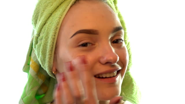 young girl with towel on hair smiles and causing face cream video