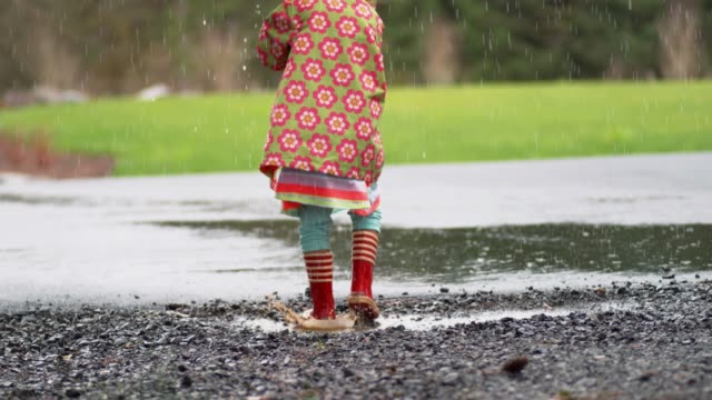 vídeos de stock e filmes b-roll de young girl with umbrella playing in rain, slow motion - poça
