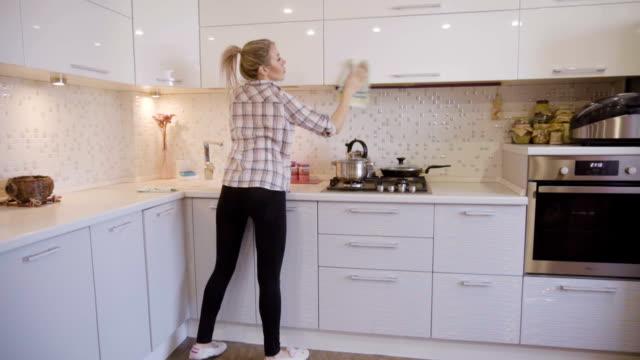 stockvideo's en b-roll-footage met jong meisje vrouw doen van huishoudelijk werk en het schoonmaken van de keuken - opruimen