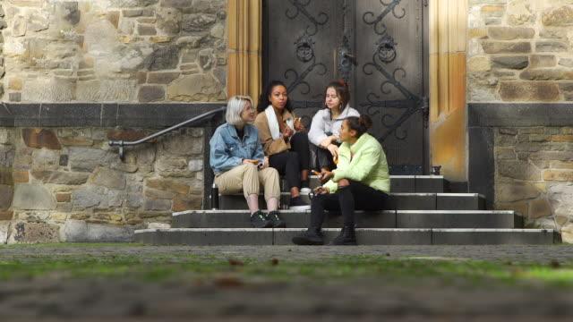 junge freundinnen essen und sprechen im freien - teenage friends sharing food stock-videos und b-roll-filmmaterial