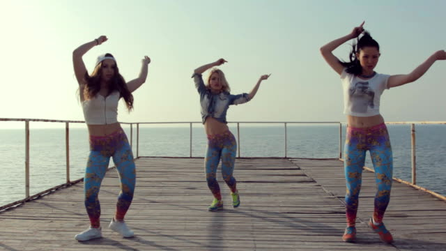 Young girls dancing modern dance on the pier near sea video