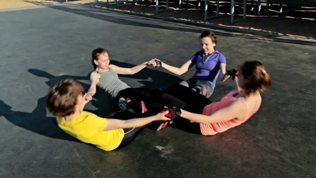 Young girls doing sit-ups exercising together video