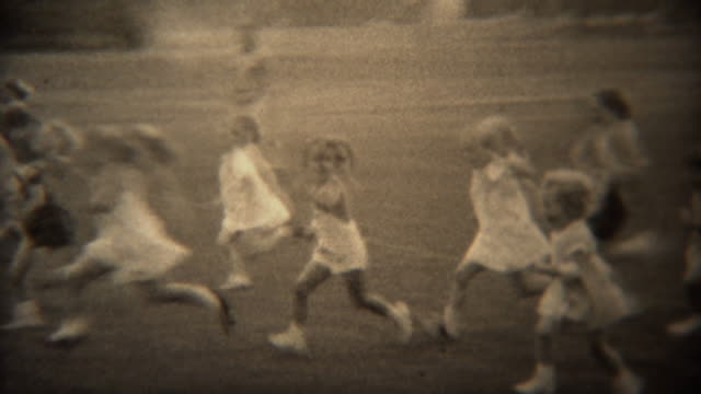 1937: Young girls foot race across grass park field in formal white dress.