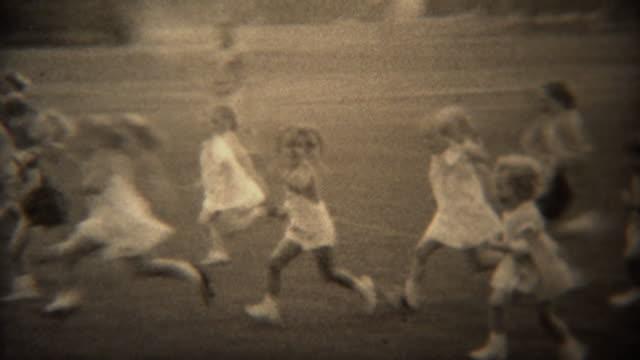 1937: 正式な白いドレスの芝生公園で若い女の子足のレース。 - アーカイブ画像点の映像素材/bロール