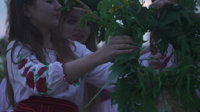 young girls in national costumes weave a wreath - славянская культура стоковые видео и кадры b-roll