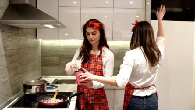 vídeos de stock e filmes b-roll de young girls in the kitchen,preparing vegan meal - avental