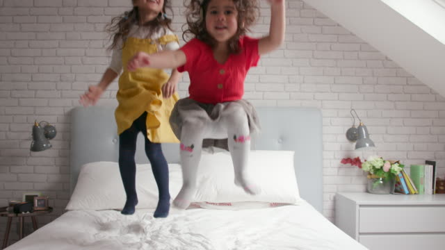 2 young girls jumping up and down on their bed and laughing