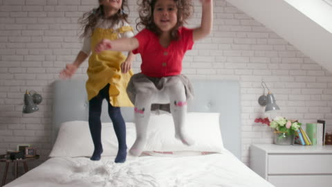 2 young girls jumping up and down on their bed and laughing 2 young girls jumping up and down on their bed and laughing together child stock videos & royalty-free footage