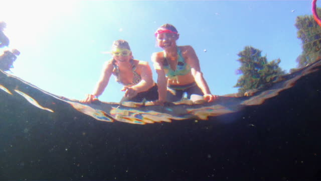 Young girls looking into water from swim dock video