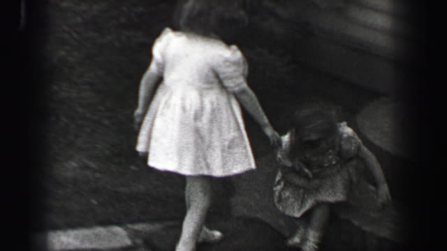 1939: young girls race over to sit on front porch stoop with wavy curly long bangs hair style. - portico video stock e b–roll