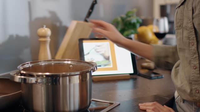 vidéos et rushes de les jeunes filles épices jusqu'à son plat qui est la cuisson dans la casserole et consulter sa tablette pour la recette. - recette
