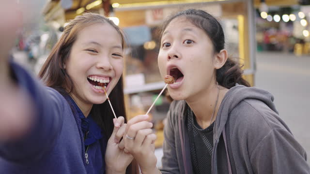 Young girls taking selfie and eating deep fried meatballs.