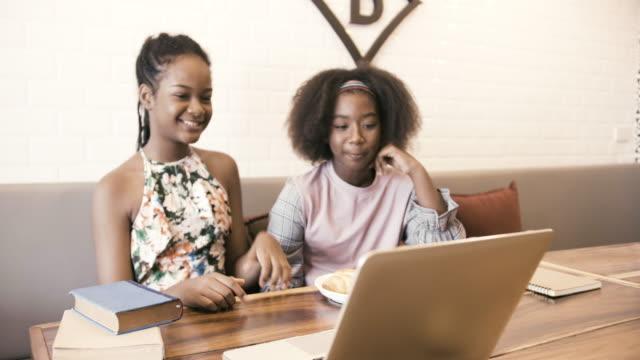 young girls watching music from notebook - кофе брейк стоковые видео и кадры b-roll
