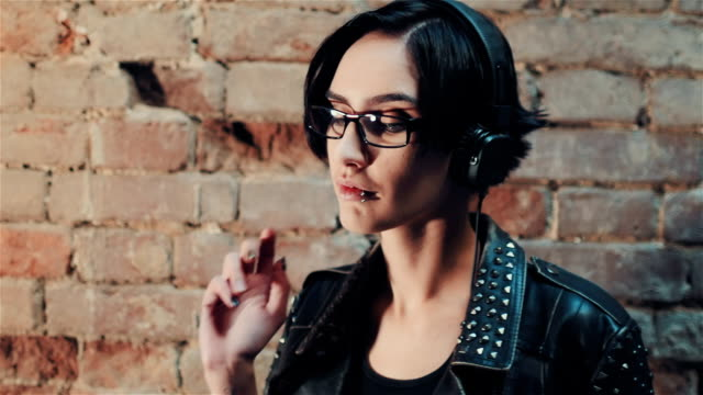 Young gothic woman listening to music on headphones. Against the background of a brick wall in an abandoned house video