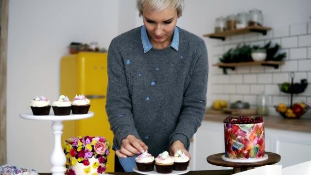 vidéos et rushes de jeune femme aux cheveux grise décorer les cupcakes avec des guimauves colorées. belle confiseur dans son atelier de cuisine moderne - boulanger