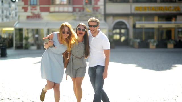 Young Group of Friends in Fashionable Sunglasses are Laughing and Looking at the Camera While Posing Outdoors on Urban Background video