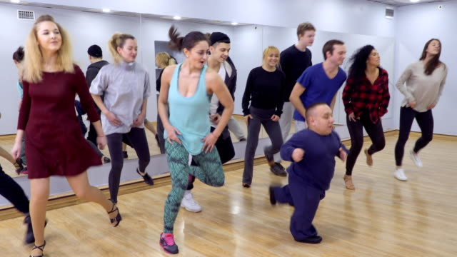 Young group of people and little man dances together in light studio A lot of people dances in front of the mirror in light studio. The dwarf man shows thumbs up and people are clapping hands after the dance. Prores codec. dance studio stock videos & royalty-free footage