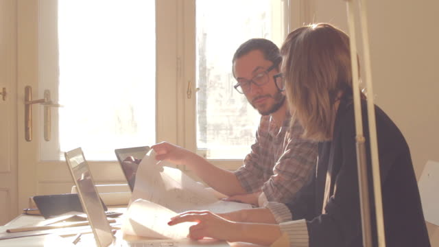 Young group of people discussing business plans, with lap-tops, plans in a room lit by natural sunlight. video