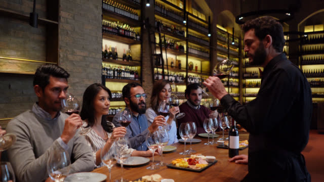 Young group of people having fun during a wine tasting paying attention to male sommelier