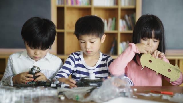 stockvideo's en b-roll-footage met jonge groep studenten in een club van de robotica plezier - kindertijd