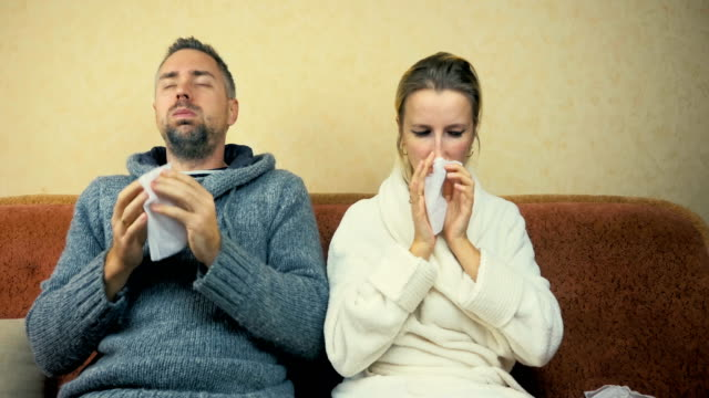 Young guy and girl sneeze and wipe snot with a handkerchief sitting at home on the sofa. video