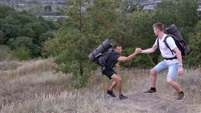 A young guy, climbing high into the mountains, reaching the top, stretches out his hand and asks for help. The man extends a helping hand to him. video