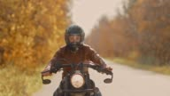 istock Young guy in a helmet rides a brutal motorcycle on an autumn road. Biker quickly rides on the highway. Portrait view. 1181501138