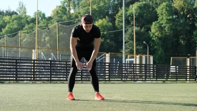 young guy in sportswear warming up at stadium. warm-up of muscles before jogging - rozgrzewka filmów i materiałów b-roll