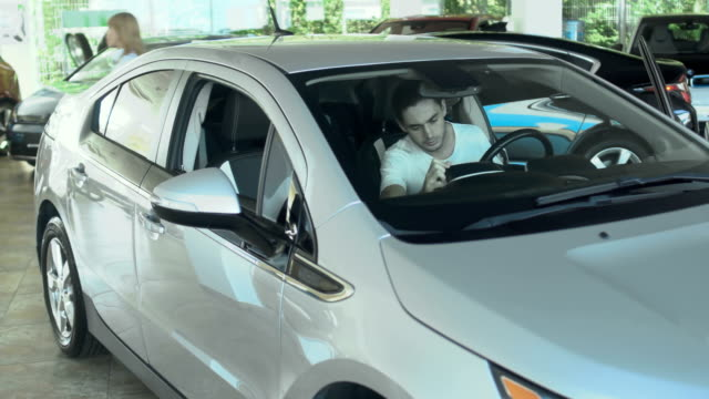 Young guy inspects auto cabin in the car dealership video