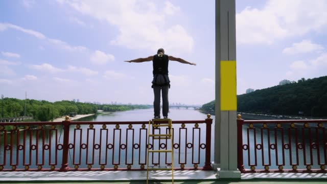 young guy jumping from a bridge with a rope for jumping - bungee jumping video stock e b–roll