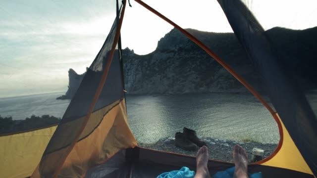 A young guy lies in a camp tent, his legs protrude from the tent. Enjoys relaxing on the beach after the adventure of the trekking day. Camp tent stands on the seashore. Hiking trip in Crimea.