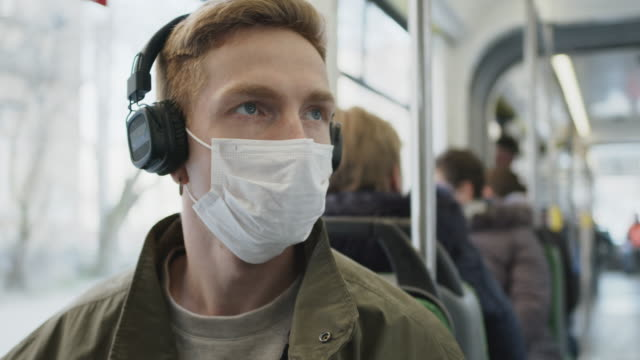 vídeos de stock e filmes b-roll de young guy rides on bus with medical mask on his face. protecting health in an epidemic. - covid hair