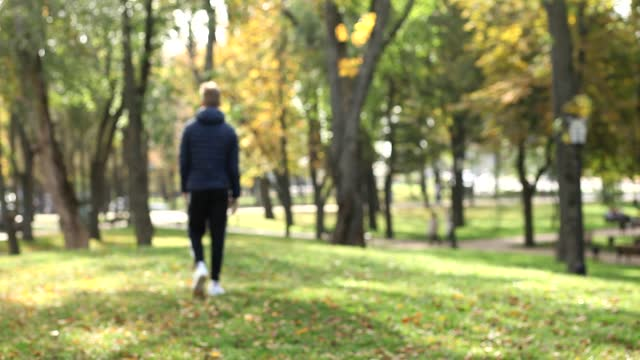 A young guy with a smartphone in his hand slowly walks into the distance of the autumn park, view from the back. Autumn concepts of loneliness, sadness or bad mood, copy space for text.