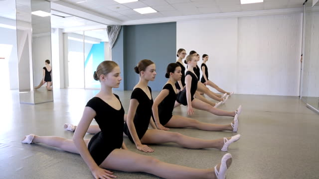 Young gymnasts sit on twine one by one in dancing class video
