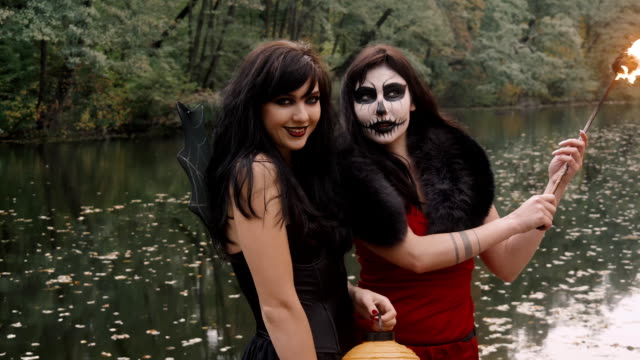Young halloween girl friends in black and red witch dress having fun in the forest park with traditional autumn holiday symbol of orange spooky pumpkin outdoor video