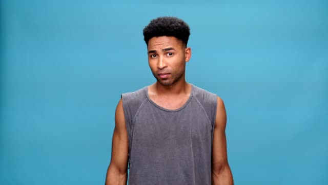 Young handsome african man showing thumbs down over blue background. video
