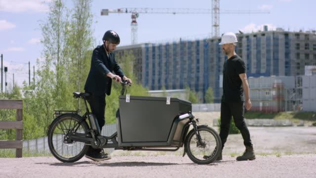 建設現場で彼の貨物のバイクで到着のハンサムな若手建築家および建設労働者を満たしています。 - プロジェクトマネージャー点の映像素材/bロール