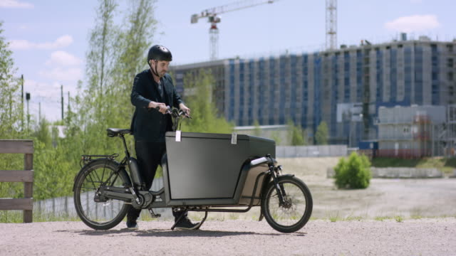 Young handsome architect arriving with his cargo bike at a construction site video