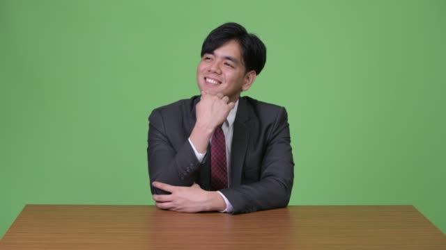 young handsome asian businessman against green background - юго восток стоковые видео и кадры b-roll