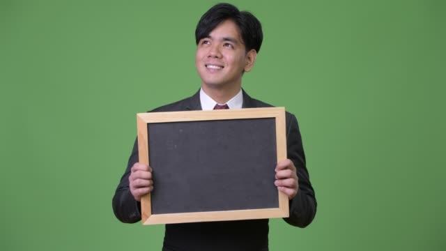 young handsome asian businessman showing blackboard - юго восток стоковые видео и кадры b-roll