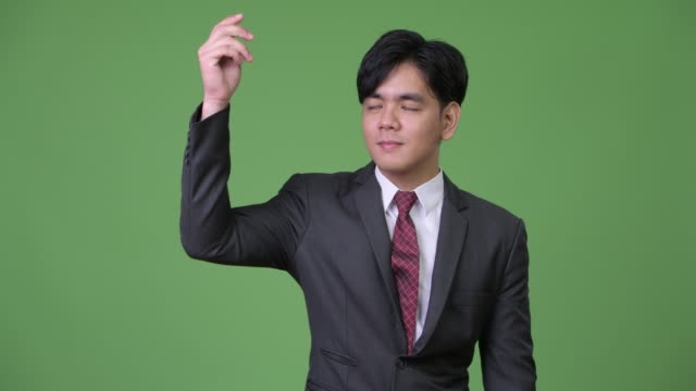 Young handsome Asian businessman showing something Studio shot of young handsome Asian businessman against chroma key with green background snapping stock videos & royalty-free footage