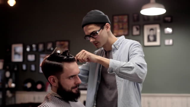Young handsome barber making haircut of attractive bearded man in barbershop video