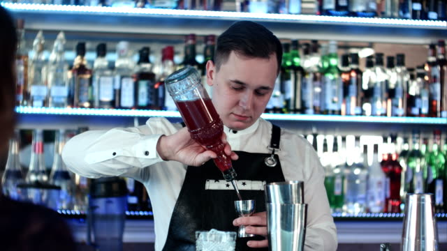 Young handsome barman in bar interior mixing alcohol cocktail video