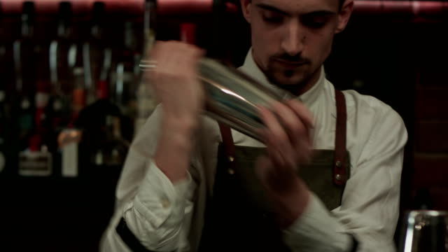 Young handsome barman in bar interior shaking and mixing alcohol cocktail video
