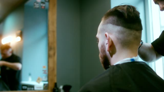 Young handsome bearded Caucasian man getting a haircut in a modern barber shop video