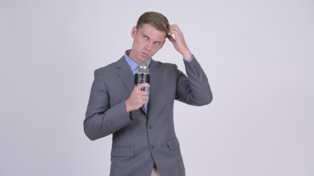 Jovem empresário loiro bonito com microfone - vídeo