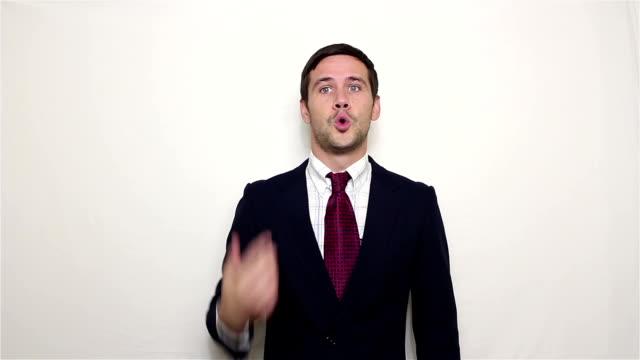 vídeos de stock, filmes e b-roll de o homem de negócios considerável novo em um terno azul está limpando o suor de sua testa com relevo. - relevo