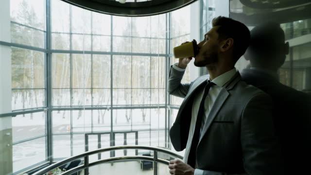 Junger hübscher Geschäftsmann im Anzug Kaffeetrinken bewegt sich in Eleavator im modernen Businesscenter – Video