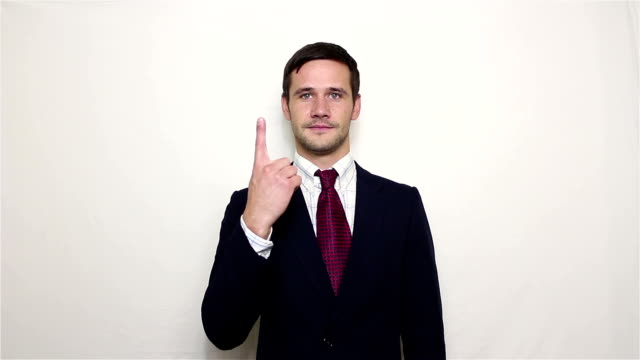 young handsome businessman is smiling and counting on his fingers up to 3. - due oggetti video stock e b–roll