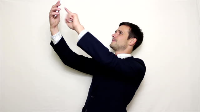 Young handsome businessman making selfie, smiling and waving his hand.